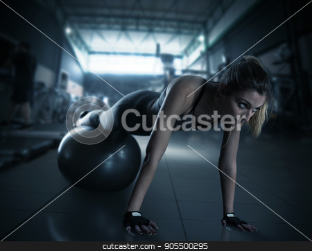 Workout with fitness ball stock photo, Muscular woman trains with fitness ball and wears sports underwear at the gym by Federico Caputo