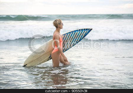 Blonde with surfboard on beach stock photo, Charming blonde girl with short hairstyle stands sideways in the water on the beach on the background of the sea and the cloudy sky. She wears orange swimsuit with sunglasses and holds the surfboard by bezikus