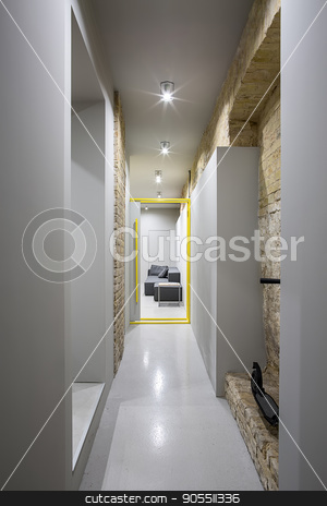 Corridor in loft style stock photo, Loft style corridor with a glowing lamps and brick and gray walls. There is a opened gray-yellow door to the room with a dark sofa and a small wooden table, black scooter on the brick wall. Vertical by bezikus