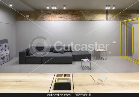 Office in loft style stock photo, Contemporary office in a loft style with gray and brick walls. There are glowing lamps, wooden tables with a niche, dark sofas with pillows, small metal tables. Horizontal by bezikus