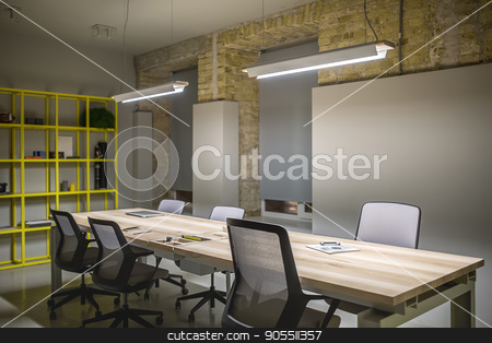 Office in loft style stock photo, Loft style workplace with gray and brick walls. There are glowing lamps over the wooden tables with black-gray chairs, metal yellow shelves, windows with dark gray curtains. Horizontal by bezikus