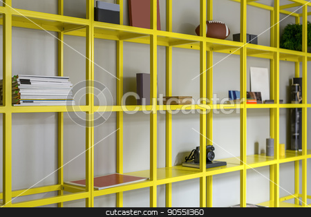 Yellow shelves with accessories stock photo, Metal yellow shelves with magazines, some books, photo camera, plant and other accessories. Closeup. Horizontal by bezikus