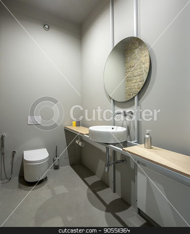 Lavatory in loft style stock photo, Restroom in a loft style with gray walls. There is a white toilet, wooden tabletops with accessories, white sink with a round mirror. Brick wall reflected in the mirror by bezikus