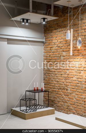 Loft style interior stock photo, Interior in a loft style with gray and brick walls. There are hanging glowing lamps, black small metal tables with candlesticks. Vertical by bezikus