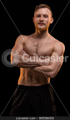 Smiling muscular man with arms crossed stock photo, Smiling muscular man with arms crossed on black background by Chris Tefme