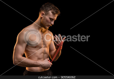 Bearded fighter man with boxing bandages stock photo, Bearded fighter man with boxing bandages on black background by Chris Tefme