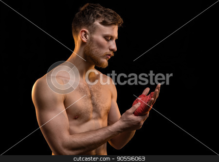 Young fighter man with boxing bandages stock photo, Young fighter man with boxing bandages on black background by Chris Tefme
