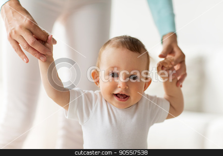 happy baby learning to walk with mother help stock photo, family, child, childhood and parenthood concept - happy little baby learning to walk with mother help at home by Syda Productions