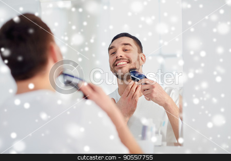 man shaving beard with trimmer at bathroom stock photo, beauty, grooming, winter, christmas and people concept - young man looking to mirror and shaving beard with trimmer or electric shaver at home bathroom over snow by Syda Productions