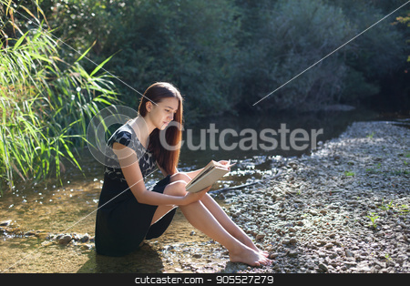 girl reading a book in the forest stock photo, girl reading a book in the forest on the banks of the river by dmitriisimakov