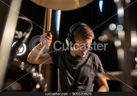 male musician playing drums and cymbals at concert stock photo, music, people, musical instruments and entertainment concept - male musician in headphones with drumsticks playing drums and cymbals at concert or studio by Syda Productions