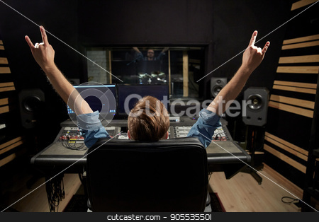 man at mixing console in music recording studio stock photo, music, technology, people and equipment concept - happy man at mixing console in sound recording studio showing rock gesture by Syda Productions