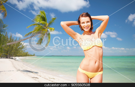 happy woman in bikini swimsuit on tropical beach stock photo, people, summer holidays, vacation and travel concept - happy young woman posing in bikini swimsuit with raised hands over exotic tropical beach with palm trees and sea shore background by Syda Productions