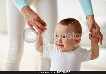 happy baby learning to walk with mother help stock photo, family, child, childhood and parenthood concept - close up of happy little baby learning to walk with mother help at home by Syda Productions