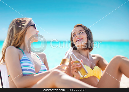 happy young women with drinks sunbathing on beach stock photo, summer holidays, vacation, travel and tourism people concept - smiling young women with drinks sunbathing on beach over sea and blue sky background by Syda Productions