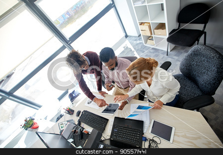 business team with tablet pc and papers at office stock photo, business, startup and people concept - international creative team with tablet pc, laptop computers and papers sitting at office table by Syda Productions