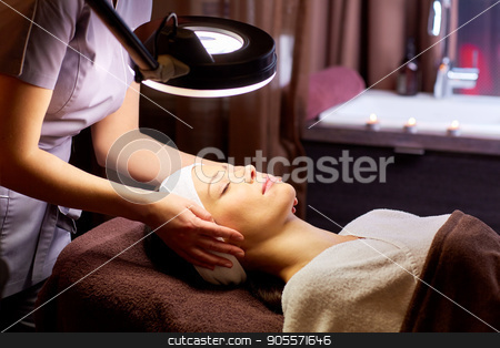beautician doing face massage to woman at spa stock photo, people, beauty, lifestyle and relaxation concept - beautician with magnifying lamp doing face massage to beautiful young woman at spa by Syda Productions