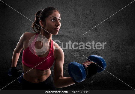 Athletic muscular woman stock photo, Athletic muscular woman training biceps with dumbbells by Federico Caputo