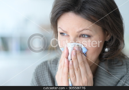 Cold young woman with a handkerchief stock photo, Portrait of a cold young woman with a handkerchief by Ruslan Huzau