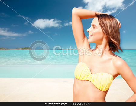 happy woman in bikini swimsuit on tropical beach stock photo, people, summer holidays, vacation and travel concept - happy young woman posing in bikini swimsuit with raised hand over exotic tropical beach background by Syda Productions