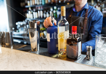 barman with shaker, alcohol and jigger at bar stock photo, alcohol drinks, people and luxury concept - barman with shaker, bottles and jigger preparing cocktail at bar by Syda Productions