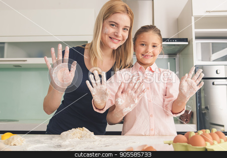 Young mother and daughter cooking dough together stock photo, Young mother and daughter cooking dough together in kitchen by Dmytro Sidelnikov