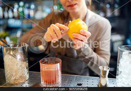 bartender peels orange peel for cocktail at bar stock photo, alcohol drinks, people and luxury concept - woman bartender with glass and peeler removing peel from orange and preparing cocktail at bar by Syda Productions