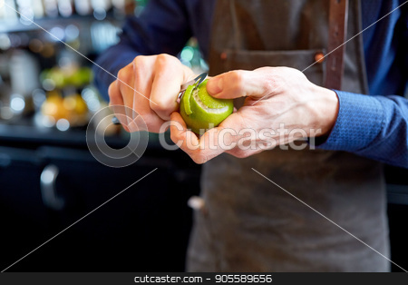 bartender removing peel from lime at bar stock photo, people and profession concept - bartender with peeler removing peel from lime at bar by Syda Productions