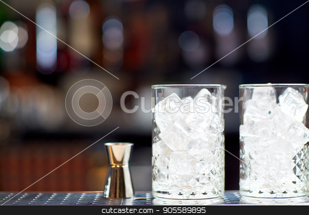 glasses with ice and jigger on bar counter stock photo, alcohol drinks and luxury concept - two vintage glasses with ice cubes and jigger on bar counter by Syda Productions