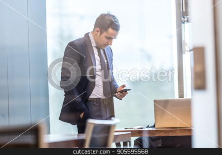 Businessman looking at smart phone in modern corporate office. stock photo, Trough the window view of businessman looking at smart phone in modern corporate office. by kasto