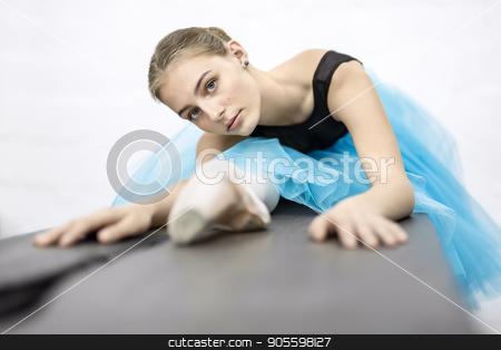 Ballerina posing in studio stock photo, Charming ballerina presses her torso to the leg on the wooden table on the white wall background in the studio. She wears a black leotard with cyan tutu and pointe shoes. Girl looks into the camera by bezikus