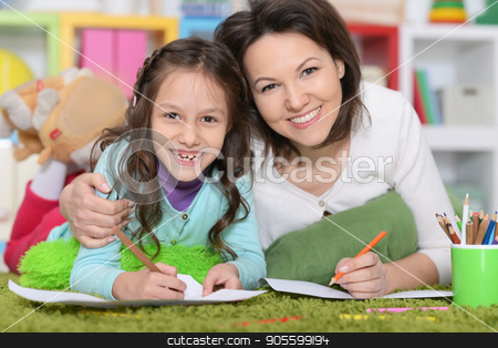Mother and daughte drawing pictures stock photo, Mother and daughter lying on floor and drawing pictures by Ruslan Huzau
