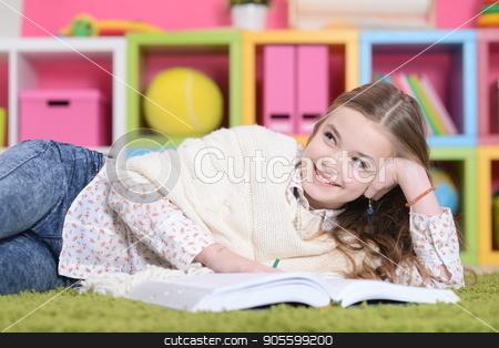 little girl lying on green carpet stock photo, Portrait of cute little girl lying on green carpet by Ruslan Huzau