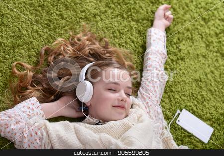 Cute little girl listening music stock photo, Cute little girl listening music with headphones by Ruslan Huzau