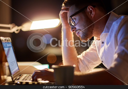 businessman typing on laptop at night office stock photo, business, overwork, people, deadline and technology concept - stressed businessman in glasses with laptop computer typing at night office by Syda Productions
