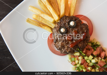 Funny meat cutlet face stock photo, Funny meat cutlet face with french fries as hair and cutted vegetables for children menu by olinchuk