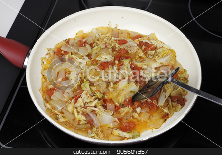 Several Vegetables Cooking in a Saucepan for Dinner stock photo, Mixed white onions, napa cabbage, red tomatoes and garlic cooking in a saucepan. Savory vegetables to serve with dinner cooking in a pan on a stove.  by Lee Serenethos