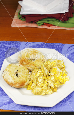 Scrambled Eggs and a Toasted Bagel Breakfast stock photo, Two halves of a toasted, buttered everything bagel on a plate with scrambled eggs. Mustard with scrambled eggs and a toasted and buttered everything bagel.  by Lee Serenethos
