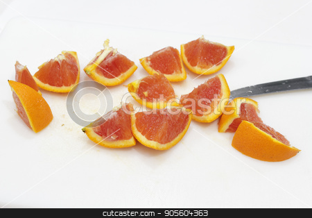 Cut Pieces of Orange on a Cutting Board stock photo, One bright orange fruit cut into twelve pieces with a knife on a white plastic cutting board close-up. An orange sliced into many chunks on a cutting board.  by Lee Serenethos