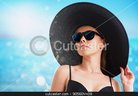 Girl with hat and sunglasses at the beach stock photo, Girl with black hat and sunglasses at the beach by Federico Caputo