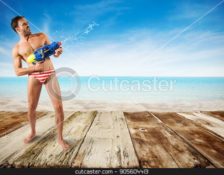 Boy play with water gun stock photo, Boy play with water gun at the beach by Federico Caputo