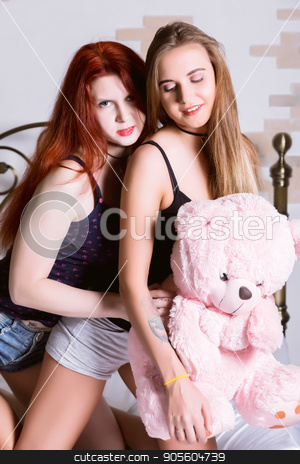 Two girlfriends huging and kissing on a bed in bright bedroom. Lesbian couple with teddy bear stock photo, Two girlfriends huging and kissing on a bed in bright bedroom. Lesbian couple. by Alexander