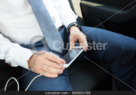 Close up of businessman using mobile smart phone in a car. stock photo, Close up of a businessman using smart phone while driving on the back seat of a car. Focus on mobile device. by kasto
