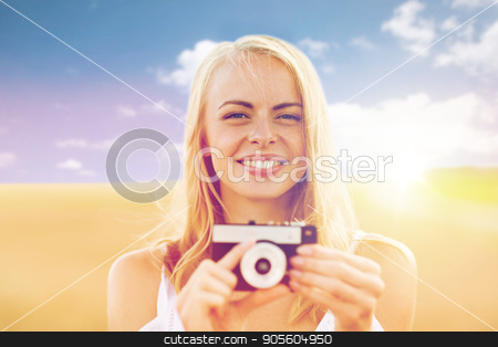 happy young woman with film camera outdoors stock photo, nature, summer holidays, vacation and people concept - happy smiling young woman with film camera outdoors by Syda Productions