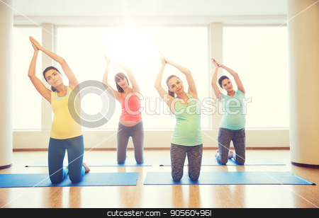 happy pregnant women exercising on mats in gym stock photo, pregnancy, sport, fitness, people and healthy lifestyle concept - group of happy pregnant women exercising on mats in gym by Syda Productions
