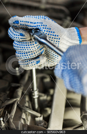 mechanic man with wrench repairing car at workshop stock photo, car service, repair, maintenance and people concept - auto mechanic man with wrench and lamp working at workshop by Syda Productions