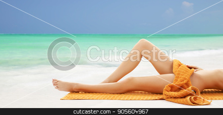 legs of bare woman lying in towel on beach stock photo, beauty, people and bodycare concept - legs beautiful bare woman lying on towel over beach background by Syda Productions