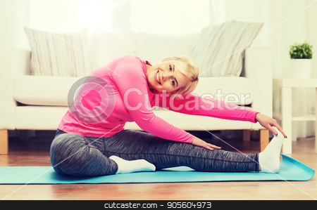 happy woman stretching leg on mat at home stock photo, fitness, sport, people and healthy lifestyle concept - happy plus size woman stretching leg on mat at home by Syda Productions