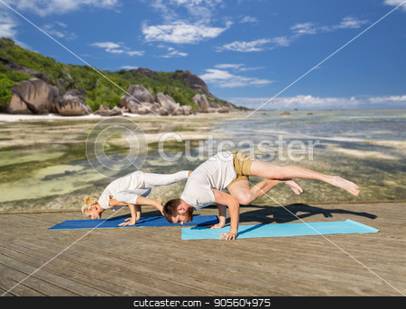people making yoga exercises outdoors stock photo, fitness, sport and healthy lifestyle concept - people making yoga exercises outdoors over exotic tropical beach background by Syda Productions