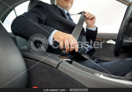 senior businessman fastening car seat belt stock photo, transport, business trip, safety and people concept - senior businessman fastening seat belt before driving car by Syda Productions